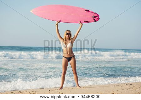 A beautiful surfer girl at the beach with her surfboard