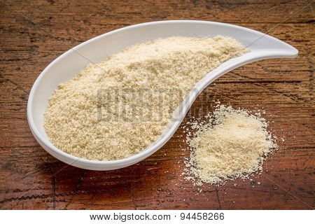 whey protein powder - a teardrop shaped bowl and a pile against rustic wood