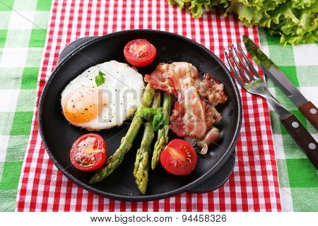 Dish of asparagus with eggs and bacon in pan on table, closeup
