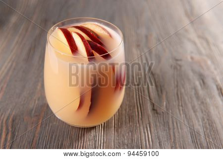 Glass of apple cider on wooden background
