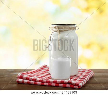 Retro can for milk and glass of milk on wooden table, on bright background