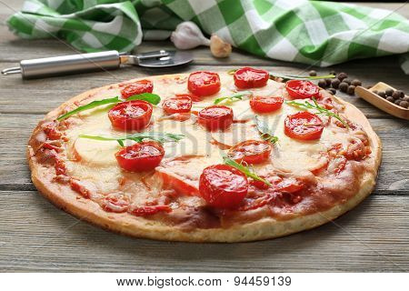 Delicious pizza with cheese and cherry tomatoes on wooden table, closeup