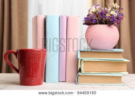Books, cup and plant on wooden table, closeup