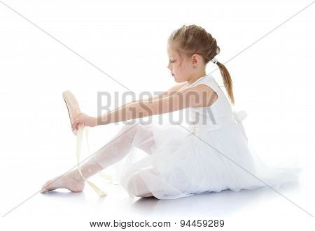 Lovely little girl acrobat or ballerina in a white dress wearing shoes
