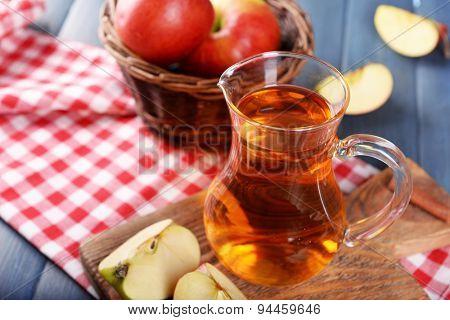 Glass jug of apple juice on wooden table, closeup
