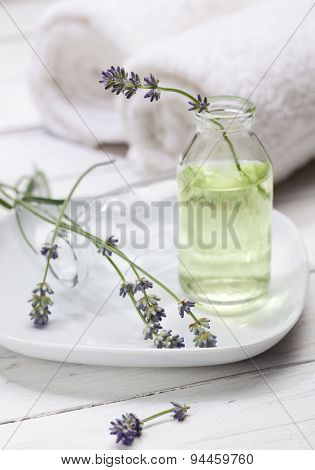 lavender flowers in bottle with essence, towels in background