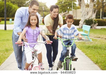 Parents Teaching Children To Ride Bikes In Park