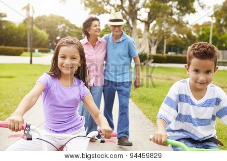 Grandparents Taking Grandchildren To Ride Bikes In Park