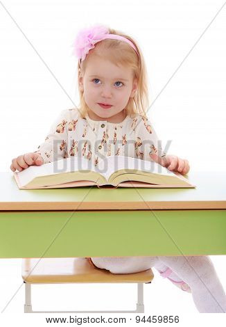 Happy joyful blonde girl is reading a thick book sitting on the table