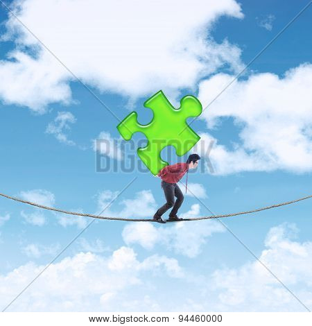 Businessman Carrying Puzzle On The Rope
