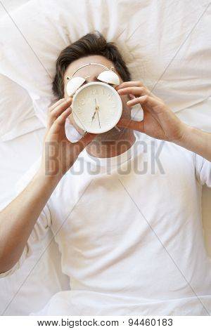 Man In Bed With Alarm Clock In Front Of Face