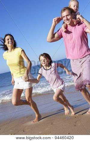 Family Running Along Beach Together
