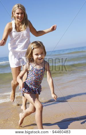 Mother Chasing Daughter Along Beach