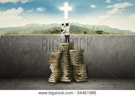 Family Standing On Book And See A Cross