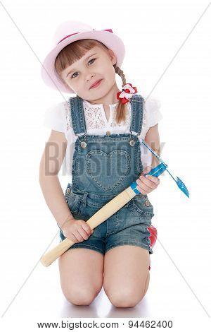 The girl is holding a garden shovel