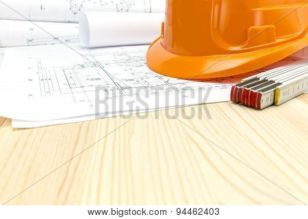Safety Helmet And Heap Of Project Drawings