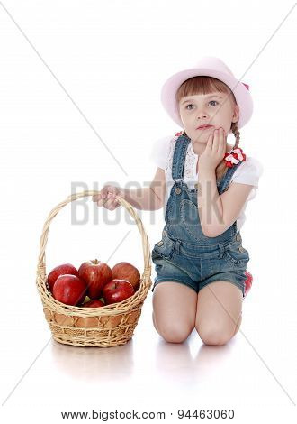 rich harvest of apples lies in the basket which keeps little girl