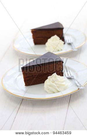 homemade sachertorte, Austrian chocolate cake isolated on white wooden background