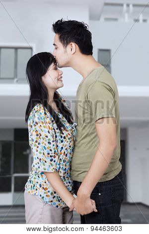 Happy Family Kissing At New Home
