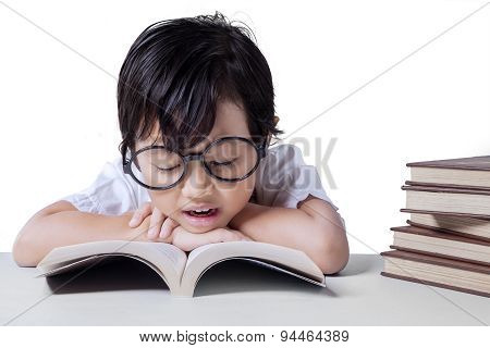 Little Girl Reads Textbook On Desk