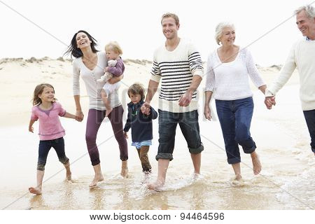 Multi Generation Family Walking Along Beach Together