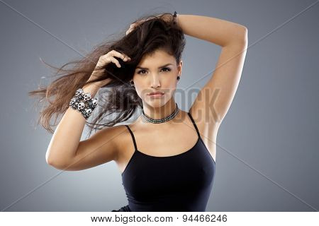 Portrait of sexy woman with windtorn long hair, looking at camera with hands in hair.