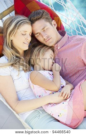 Family Sleeping In Garden Hammock Together