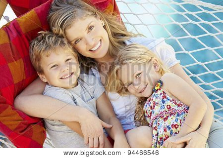 Mother And Children Relaxing In Garden Hammock Together