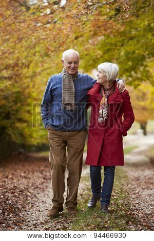 Senior Couple Walking Along Autumn Path