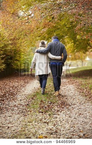 Rear View Of Couple Walking Along Autumn Path