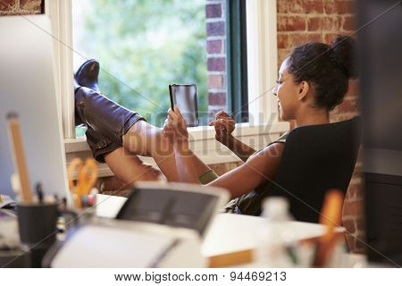 Businesswoman With Digital Tablet Relaxing In Modern Office