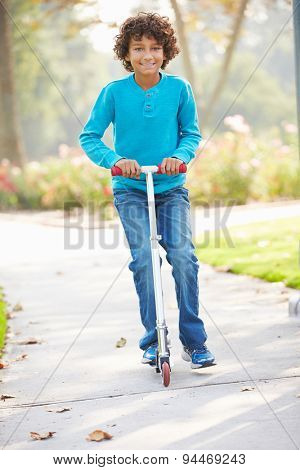 Young Boy Riding Scooter In Park