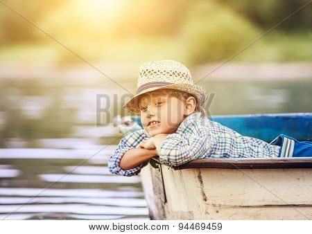 Dreaming Boy Lying In Old Boat On The River