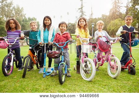 Young Children With Bikes And Scooters In Park