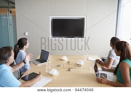 Four Businesspeople Having Video Conference In Boardroom