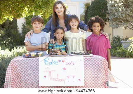 Group Of Children Holding Bake Sale With Mother