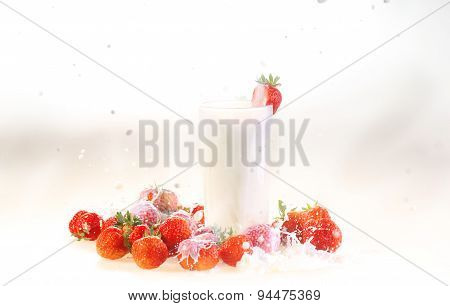 Milk In A Transparent Glass And A Strawberry On A White Background