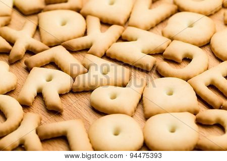 Baked letter cookie over the wooden table