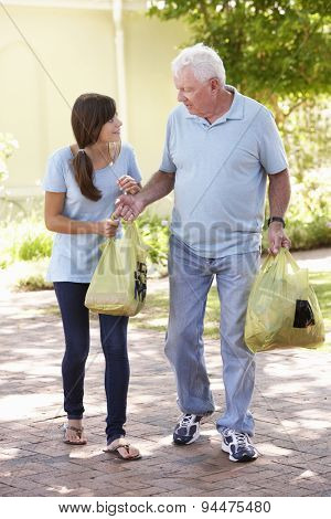 Teenage Granddaughter Helping Grandfather With Shopping
