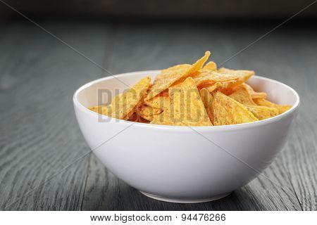 tortilla chips in white bowl on wooden table