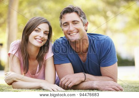 Romantic Couple Lying On Grass In Summer Park