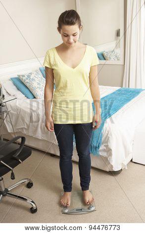 Teenage Girl Standing On Scales In Bedroom