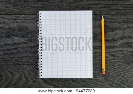 blank notepad with chequered pages on gray wood table and pencil