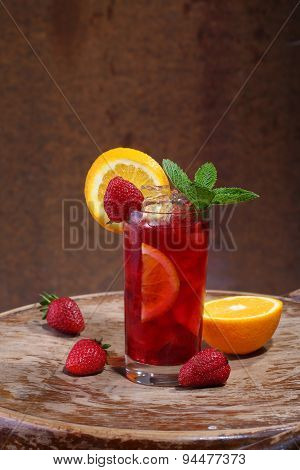 Wine Of Sangrija In A Transparent Glass With A Strawberry, An Orange And Mint