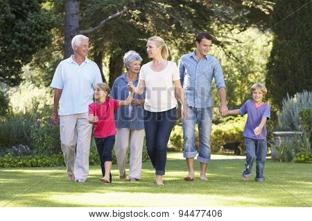 Three Generation Family Walking In Garden Together