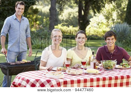 Teenage Family Enjoying Barbeque In Garden Together