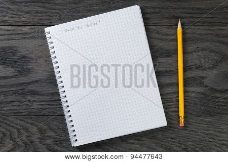 back to school phrase in notepad with chequered pages on gray wood table and pencil