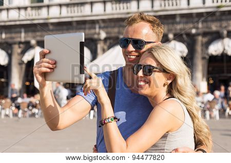 Couple traveling and using tablet computer
