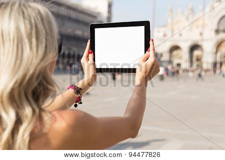Tourist taking photo with tablet computer with empty white screen