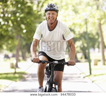 Mature Man Cycling Through Park